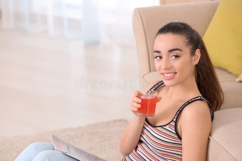 Suco bebendo do citrino da jovem mulher bonita ao ler o compartimento em casa fotografia de stock royalty free