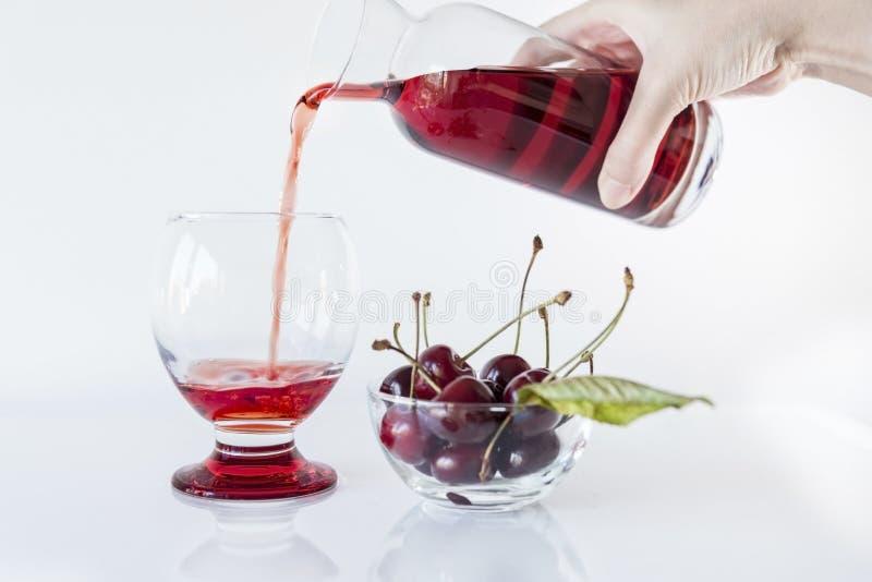 Suco da cereja ácida que derrama em um vidro em um fundo branco com uma bacia de cereja ácida, fim acima fotos de stock royalty free