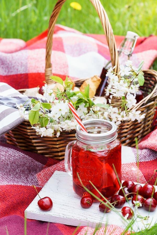 Suco da cereja na cesta do frasco e do piquenique de pedreiro com alimento, flores imagens de stock