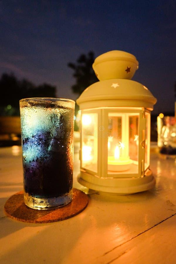 Suco da ervilha de borboleta com vela na lâmpada fotografia de stock royalty free