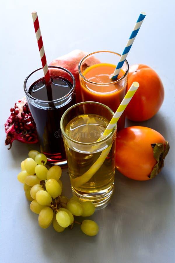 Suco da romã, do caqui e de uva no fundo de madeira cinzento Conceito saudável comer imagem de stock