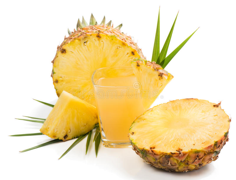 Suco de abacaxi em um vidro e em um abacaxi imagem de stock royalty free