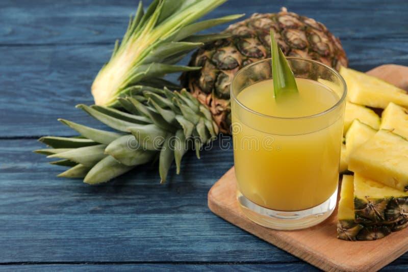 Suco de abacaxi em um vidro e em partes de abacaxi fresco em um fundo de madeira azul ver?o Frutas fotos de stock royalty free