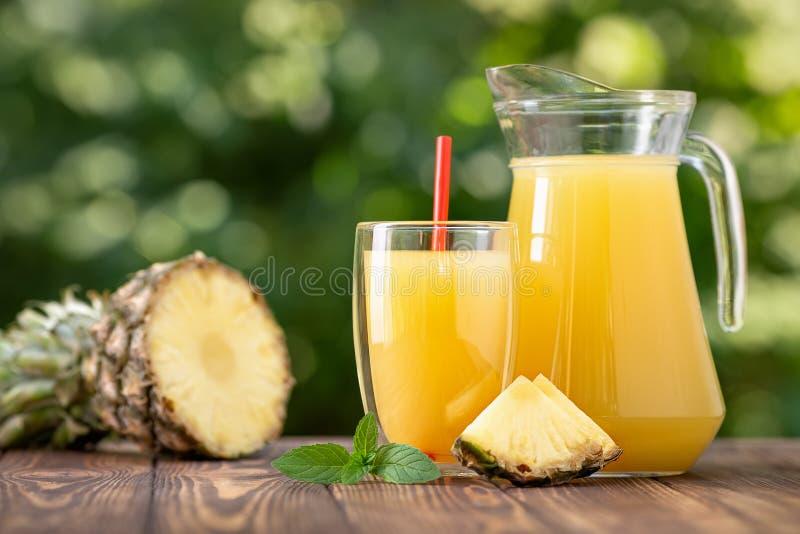 Suco de abacaxi no vidro e no jarro imagem de stock