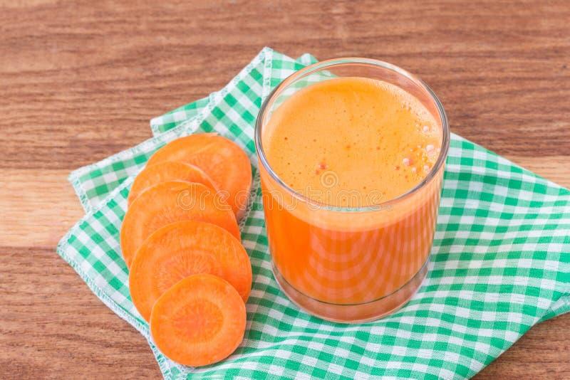 Suco de cenoura fresco no vidro e no vegetal cortado da cenoura no guardanapo na tabela de madeira imagem de stock