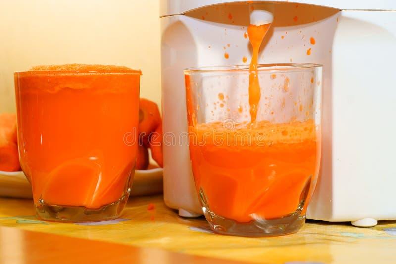 Suco de cenoura no vidro, juicer imagem de stock