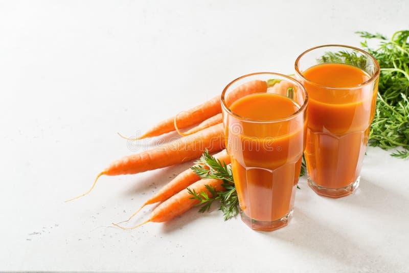 Suco de cenouras nos vidros no fundo de pedra branco com as cenouras cruas e frescas imagens de stock royalty free
