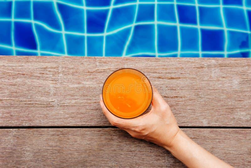Suco de fruta do verão Mulher que relaxa na piscina em seu V imagens de stock