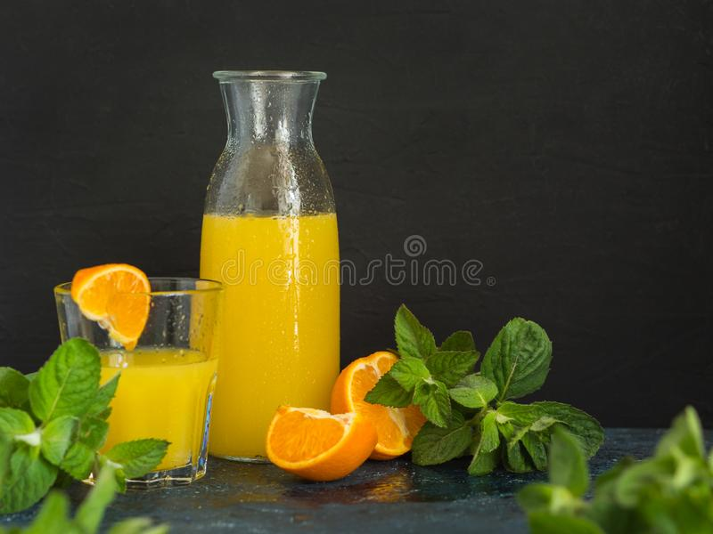 Suco de fruta saud?vel Suco espremido fresco natural da laranja ou da tangerina em uma garrafa de vidro com gotas da água e a hor imagens de stock royalty free