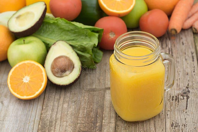 Suco de fruto no frasco de vidro Fundo verde, tabela de madeira Legumes frescos e frutos - abacate, maçã, tomates Saudável, fotografia de stock royalty free