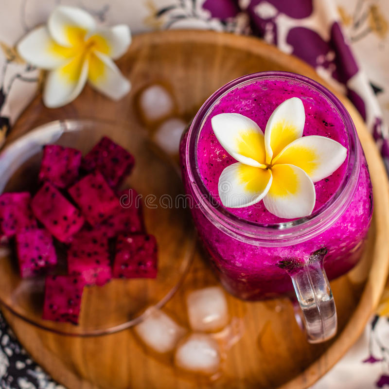 Suco de fruto vermelho do dragão em um vidro, decorado com flor do Plumeria, fruto cortado do dragão e cubos de gelo Servido em u imagem de stock