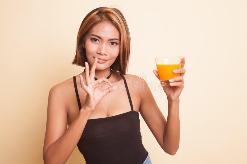 Suco de laranja asiático novo da bebida da APROVAÇÃO da mostra da mulher fotografia de stock