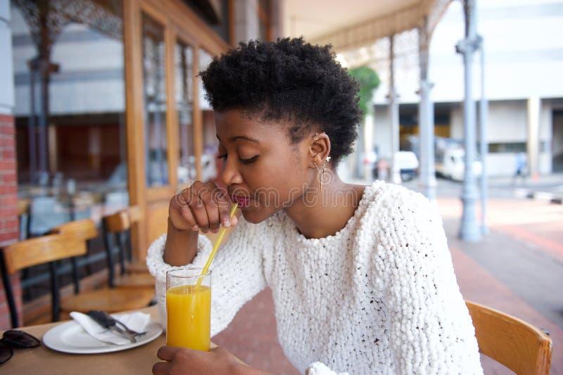 Suco de laranja bebendo da mulher africana no café exterior imagem de stock