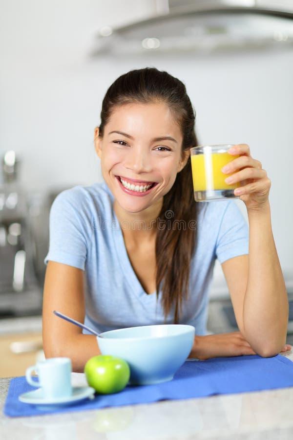 Suco de laranja bebendo da mulher que come o café da manhã foto de stock royalty free