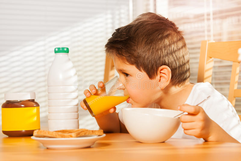 Suco de laranja bebendo do rapaz pequeno no café da manhã imagem de stock