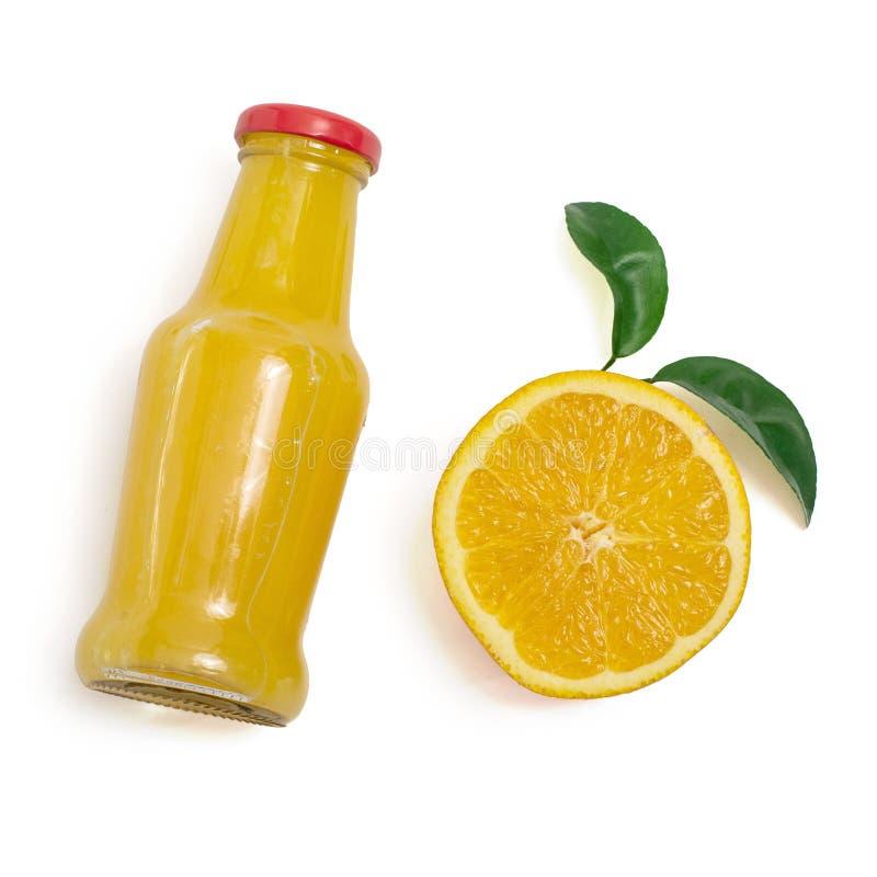 Suco de laranja delicioso em uma garrafa e em uma fatia de laranja ao lado dela Isolado no branco Vista superior imagens de stock royalty free