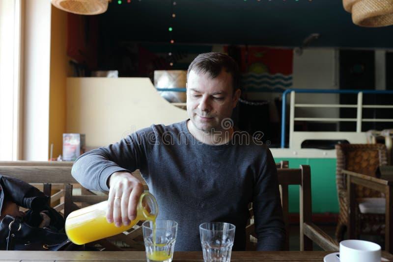 Suco de laranja de derramamento do homem foto de stock royalty free