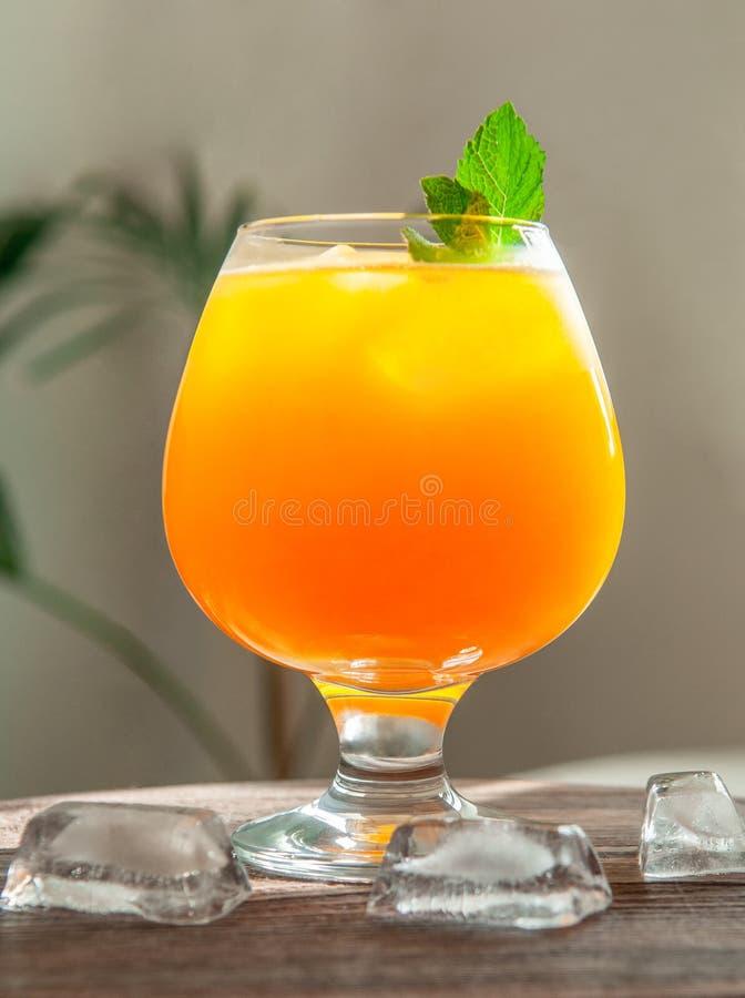 Suco de laranja em um vidro de aguardente com um ramo da hortel? Em um fundo de madeira Ao lado de um vidro de cubos de gelo Fund imagem de stock