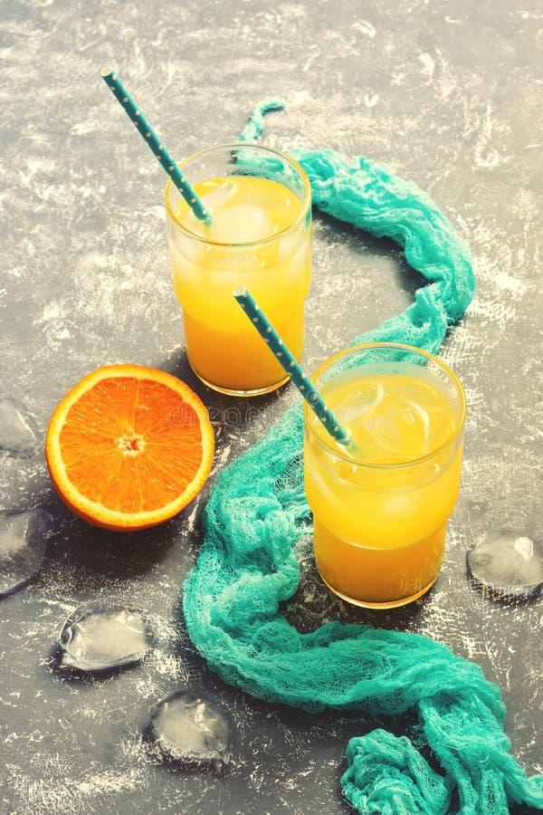 Suco de laranja em um vidro com um guardanapo azul em um fundo cinzento Escolha seletiva O conceito do verão Foto tonificada imagens de stock royalty free
