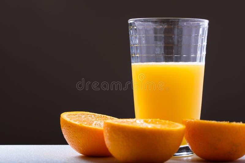 Suco de laranja fresco no vidro com corte da laranja na opinião lateral das metades no fundo escuro imagem de stock royalty free