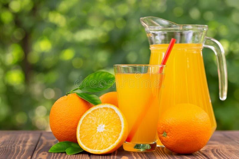 Suco de laranja no vidro e no jarro fotografia de stock