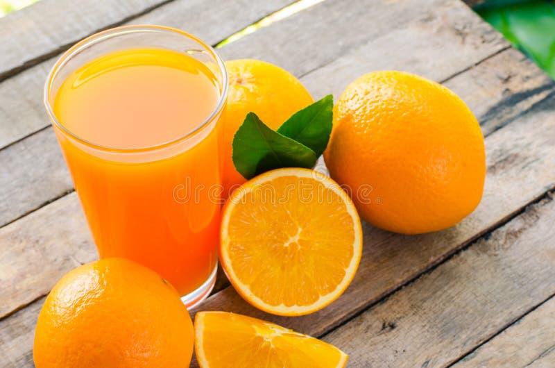 Suco de laranja no vidro, frutos frescos no fundo de madeira foto de stock
