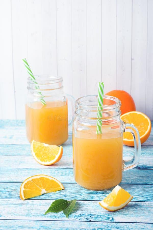 Suco de laranja nos frascos de vidro e em laranjas frescas em um fundo azul fotografia de stock royalty free