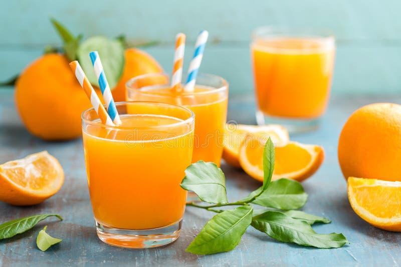Suco de laranja nos frutos de vidro e frescos com as folhas no fundo de madeira foto de stock royalty free