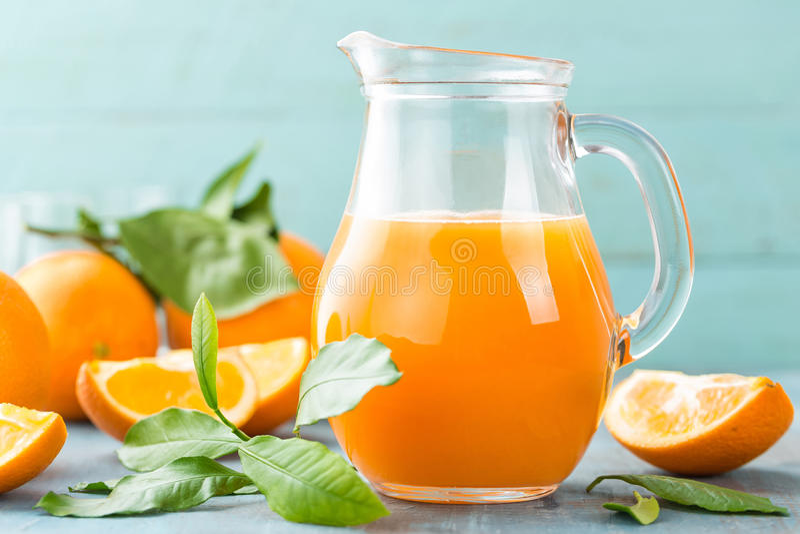 Suco de laranja nos frutos de vidro e frescos com as folhas no fundo de madeira imagens de stock royalty free