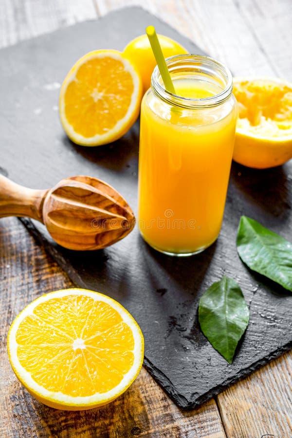 Suco de laranja recentemente espremido na garrafa de vidro no backgrou de madeira fotos de stock royalty free