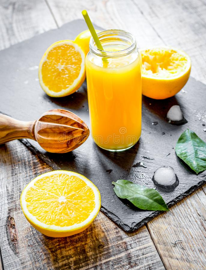 Suco de laranja recentemente espremido na garrafa de vidro no backgrou de madeira fotografia de stock royalty free