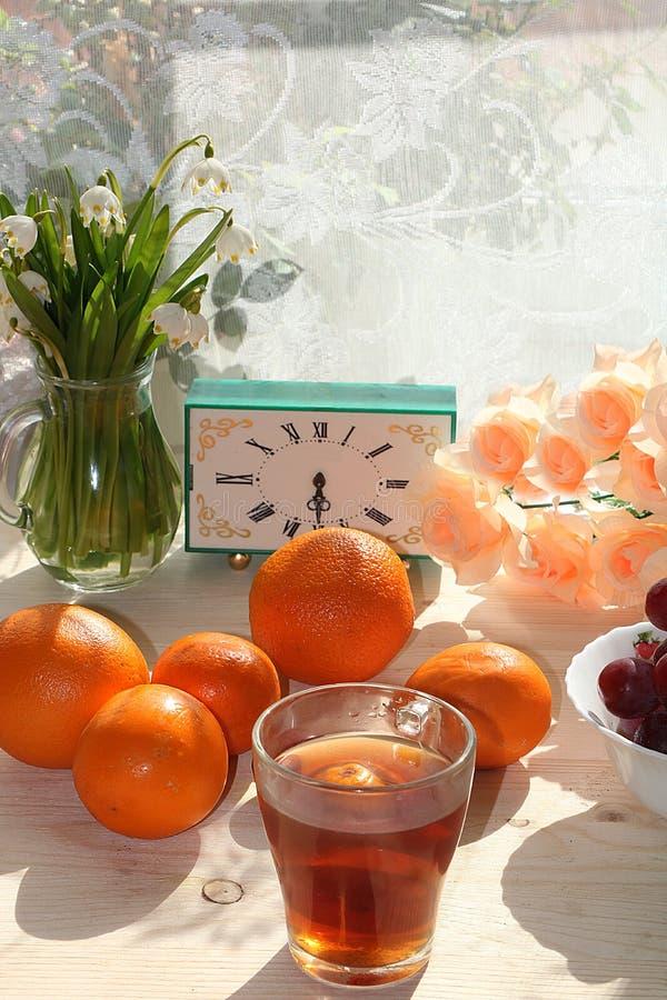 Suco de laranja, snowdrops e citrinas cedo na manhã em um fundo ensolarado fotos de stock royalty free