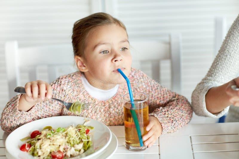Suco de maçã bebendo da menina no restaurante fotos de stock royalty free