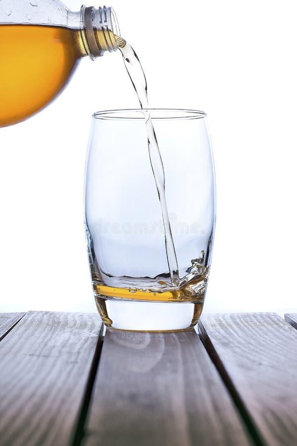 Suco de maçã fresco de derramamento no vidro claro fotos de stock