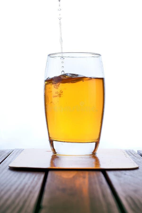 Suco de maçã fresco de derramamento no vidro claro imagem de stock