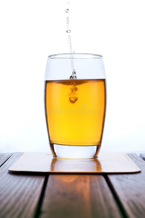 Suco de maçã fresco de derramamento no vidro claro imagens de stock