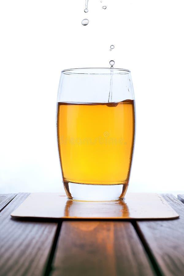 Suco de maçã fresco de derramamento no vidro claro fotos de stock royalty free