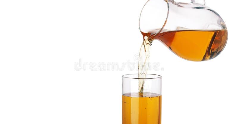 Suco de maçã que derrama do jarro no vidro, isolado no fundo branco fotos de stock royalty free