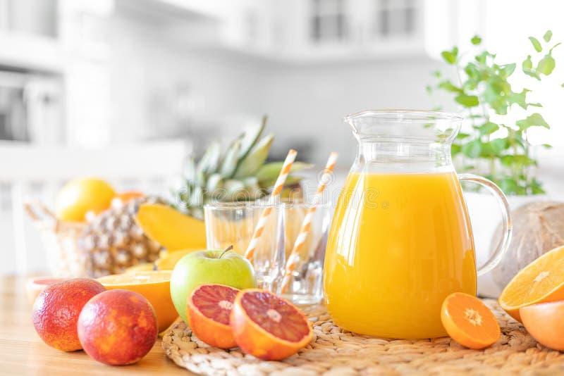Suco de Multifruit e fruto fresco na tabela no fundo da cozinha foto de stock