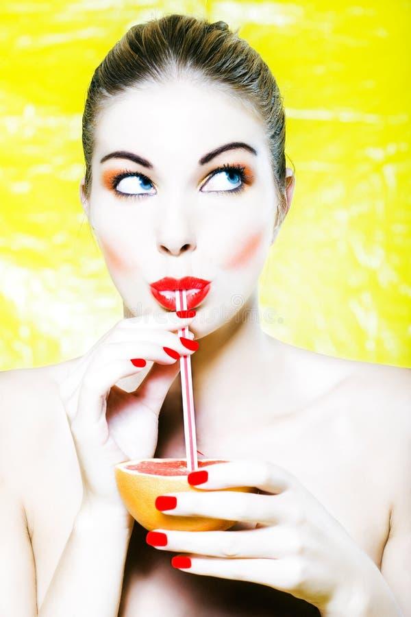 Suco de pamplumossa bebendo da mulher fotografia de stock