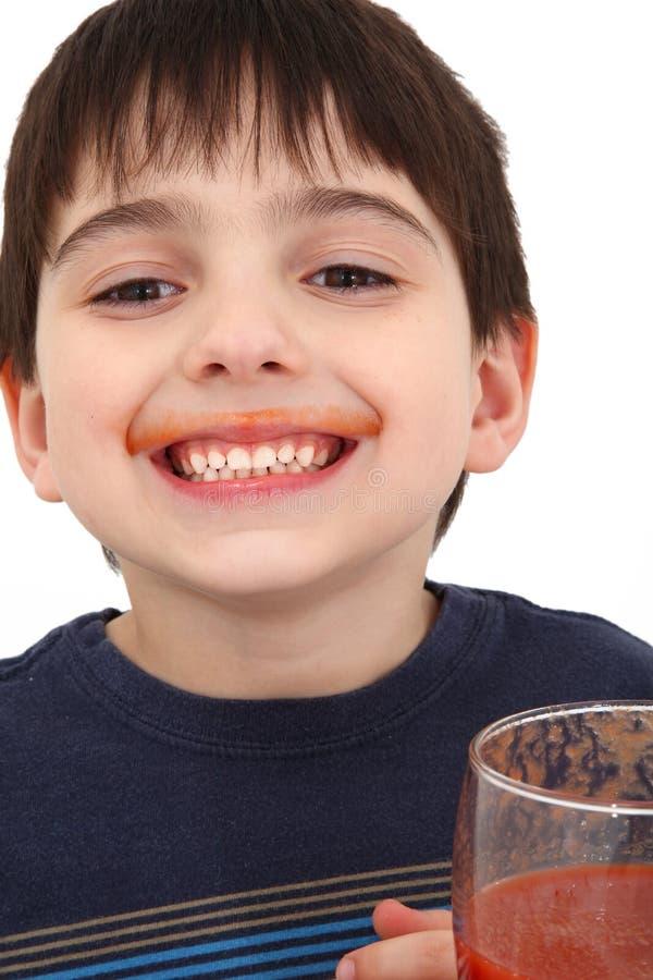 Suco de tomate bebendo do menino foto de stock