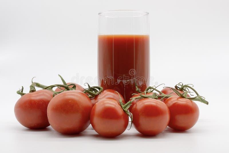 Suco de tomate delicioso e uma m?o completamente dos frutos imagem de stock