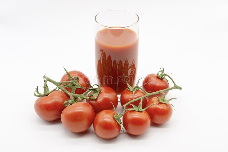 Suco de tomate delicioso e uma m?o completamente dos frutos foto de stock royalty free