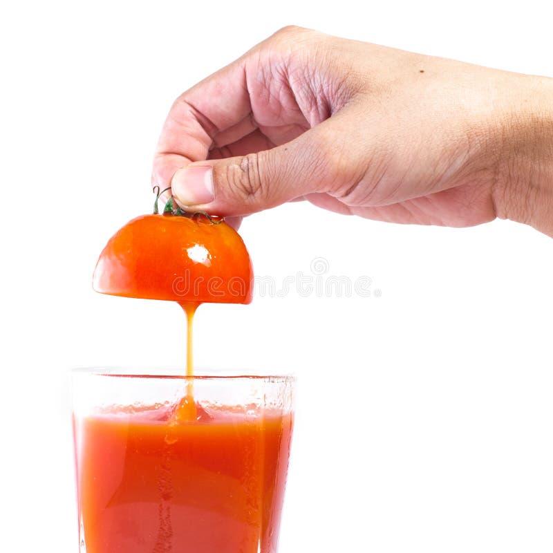 Suco de tomate fresco que derrama no vidro imagens de stock