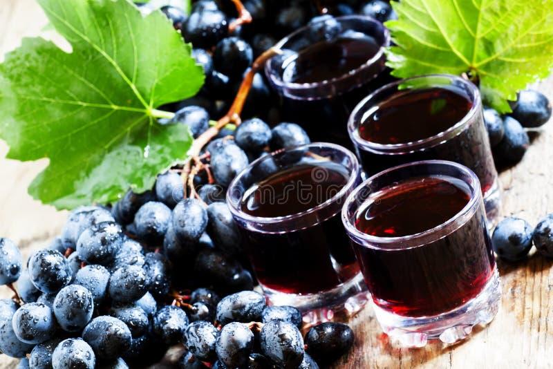 Suco de uva escuro fresco e bagas frescas na tabela de madeira velha, SE foto de stock