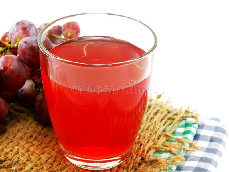 Suco de uva vermelha com o fruto isolado no fundo branco imagem de stock