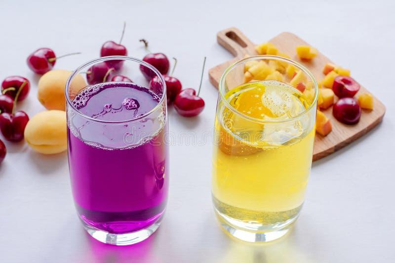 Suco do abricó e da cereja, abricós, cereja em uma tabela ensolarada Bebidas e frutos do verão Suco no suco do vidro, da cereja e imagens de stock royalty free