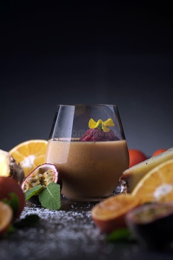 Suco do batido do cocktail de fruto em um vidro transparente na tabela, nas laranjas e nas tangerinas com abacaxi e paixão fotografia de stock royalty free