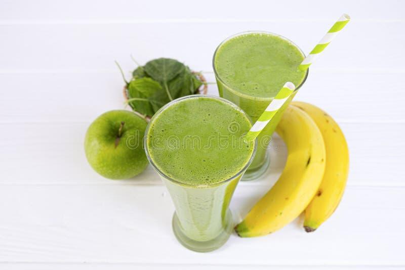 Suco dos batidos dos espinafres da banana e bebida verde do suco saudáveis imagens de stock royalty free