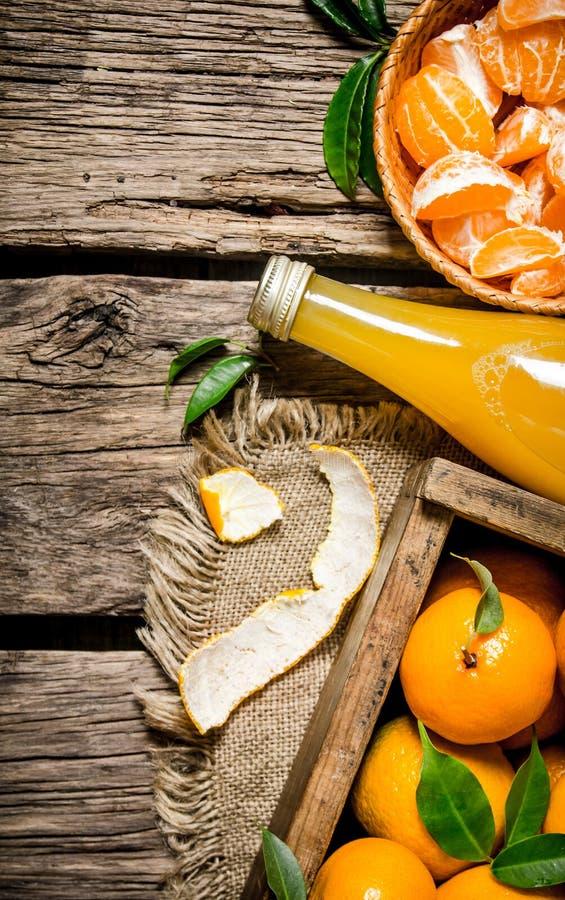 Suco em uma garrafa, em uma caixa dos mandarino e em tangerinas, dadas no copo imagens de stock royalty free